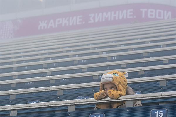Болельщица грустит на трибуне перед началом гонки с масс-старта в соревнованиях по биатлону среди мужчин на XXII зимних Олимпийских играх в Сочи.