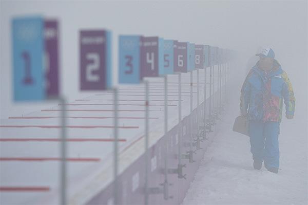 """Сотрудник лыжно-биатлонного комплекса """"Лаура"""" перед началом гонки с масс-старта в соревнованиях по биатлону среди мужчин на XXII зимних Олимпийских играх в Сочи."""