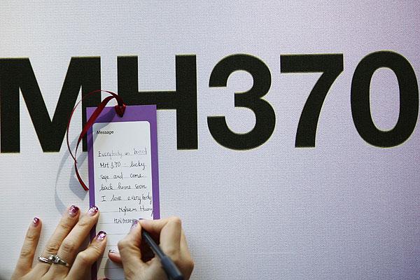 """Туристка из Вьетнама оставляет записку на бирке у """"стены надежды"""" в аэропорту Куала-Лумпура."""