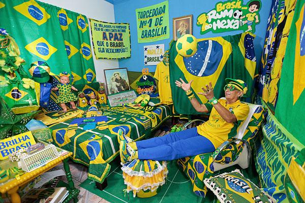 Бразильская футбольная фанатка играет с мячом в своем доме.