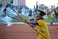 Бразильский индеец направляет свою стрелу в полицейских, которые пытаются помешать демонстрантам попасть на стадион Манэ Гарринчи.