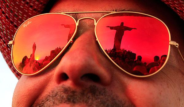 Статуя Христа-Искупителя отражается в стеклах очков одного из туристов.