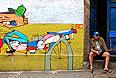 """Мужчина с плеером и йоркширским терьером сидит рядом с граффити в районе Санта Тереса в Рио-де-Жанейро. Фотография - часть проекта """"На обочине"""", обобщающего видение ЧМ-2014 зарубежными фотографами."""