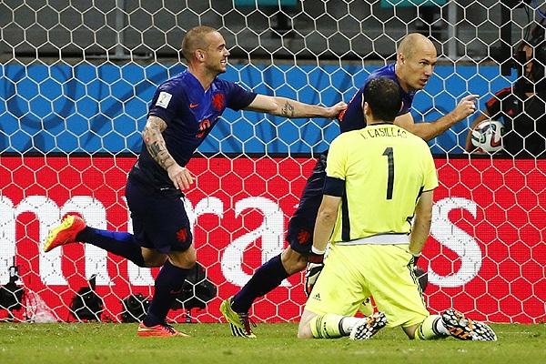 Футболисты сборной Голландии Уэсли Снейдер (слева) и Арьен Роббен (справа на втором плане) празднуют гол в ворота капитана сборной Испании Икера Касильяса (на первом плане).