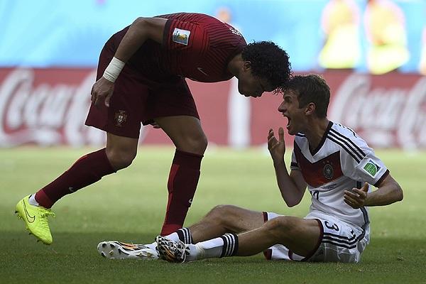 Футболист сборной Португалии Пепе (слева) нарушил правила против полузащитника команды Германии Томаса Мюллера и был удален с поля в матче группы G.