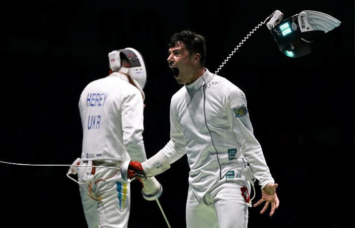Швейцарец Фабиан Каутер празднует победу над украинцем Анатолием Гереем в соревновании по фехтованию на шпагах в матче 1/16 финала