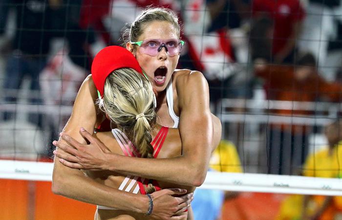 Игроки канадской сборной по пляжному волейболу Сара Паван и Хизер Бэнсли во время матча против Швейцарии