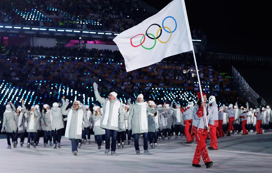 Сборная олимпийских атлетов из России принимает участие в параде стран-участниц под нейтральным флагом, который несет волонтер оргкомитета Игр