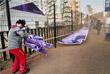 Олимпийский работник укрывается от сильных порывов ветра в олимпийской деревне в Канныне