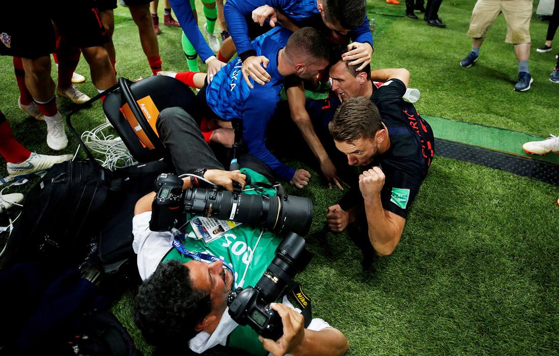 Игроки сборной Хорватии завалились на фотографа Юри Кортес из агентства AFP, празднуя второй гол в ворота Англии в полуфинале (2:1)