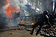 Антиправительственные демонстранты бросают камни и  бутылки с зажигательной смесью во время атаки на офис Партии регионов.