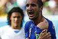 Защитник сборной Италии Джорджо Кьеллини показывает следы зубов уругвайского нападающего Луиса Суареса.